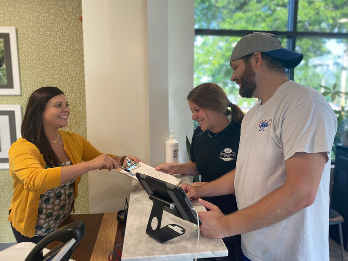 chiropractic staff helping patients at front desk
